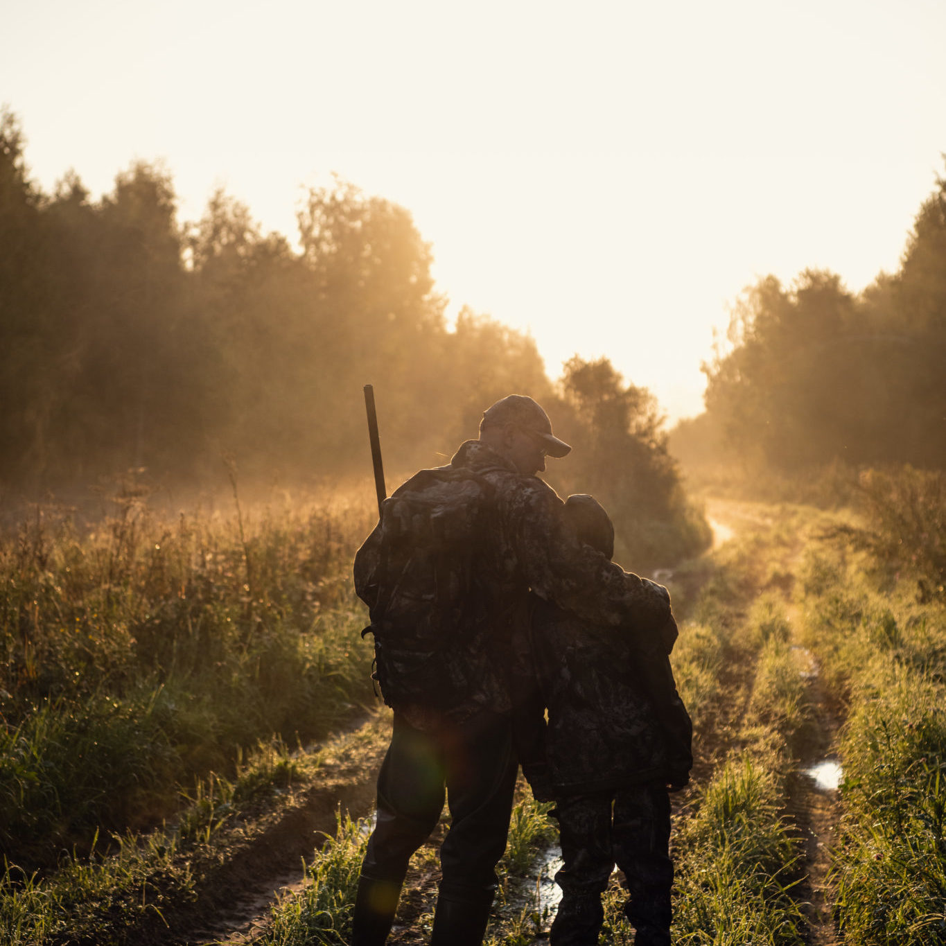 Rifle Hunter and His Son Silhouetted in Beautiful Sunset. Huntsman with a boy and rifle in a forest on a sunrise.